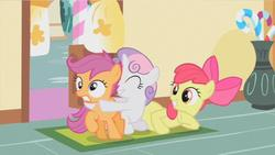Size: 853x481 | Tagged: safe, screencap, apple bloom, scootaloo, sweetie belle, earth pony, pegasus, pony, unicorn, the cutie mark chronicles, cutie mark crusaders, derp, eyes closed, female, filly, frown, grin, gritted teeth, hape, hug, prone, raised hoof, sitting, smiling, squee, sugarcube corner, wide eyes