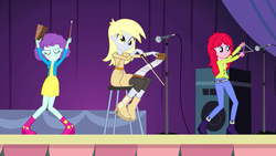 Size: 1280x720 | Tagged: safe, screencap, blueberry pie, derpy hooves, raspberry fluff, equestria girls, rainbow rocks, background human, cowbell, kimber benton, musical instrument, musical saw, saw, smiling, stage, the muffins, triangle, trio