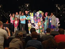 Size: 1024x768 | Tagged: safe, artist:whiteheather, human, 2014, auction, cathy weseluck, charity, convention, everfree northwest, irl, irl human, marÿke hendrikse, photo, quilt, stage