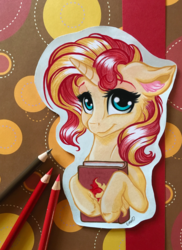 Size: 2812x3860   Tagged: safe, artist:emberslament, artist:gaelledragons, sunset shimmer, pony, unicorn, book, collaboration, colored pencil drawing, craft, cute, female, floppy ears, looking at you, mare, photo, shimmerbetes, smiling, solo, traditional art, unshorn fetlocks