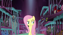 Size: 1280x720 | Tagged: safe, screencap, fluttershy, maulwurf, pony, yeti, school raze, background monster, cage, female, mare, prisoner, raised eyebrow, smiling, smirk, snowbutt mctwinkles, tartarus