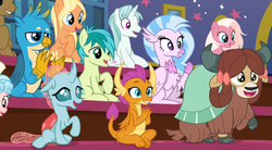 Size: 1619x893 | Tagged: safe, screencap, amber grain, clever musings, cozy glow, fuchsia frost, gallus, ocellus, sandbar, silverstream, smolder, snowy quartz, yona, changedling, changeling, dragon, earth pony, griffon, hippogriff, pegasus, pony, unicorn, yak, a rockhoof and a hard place, background pony, cheering, clapping, dragoness, female, friendship student, malachite (sailor moon), male, mare, raised hoof, sitting, stallion, student six