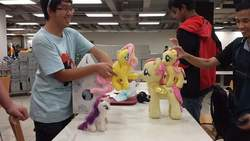 Size: 720x405 | Tagged: safe, photographer:horseplease, fluttershy, rarity, human, hoofbump, irl, irl human, malaysia, multeity, photo, plushie, so much flutter
