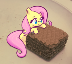Size: 706x624 | Tagged: safe, artist:burgeroise, fluttershy, pony, chocolate, cute, female, food, irl, mare, no pupils, photo, ponies in food, ponies in real life, quadratini, shyabetes, sitting, size difference, smiling, solo, three quarter view, tiny, tiny ponies, wafer
