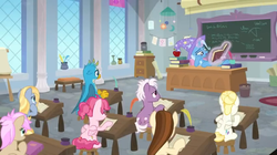Size: 1600x898 | Tagged: safe, screencap, bifröst, dawnlighter, gallus, goldy wings, loganberry, strawberry scoop, summer breeze, trixie, griffon, pony, a horse shoe-in, book, bored, chalk, chalkboard, classroom, clothes, desk, easel, female, friendship student, hat, hoof on cheek, inkwell, levitation, magic, male, mare, paper, quill, reading, school of friendship, scroll, teacher's desk, teenager, telekinesis, trash can, trixie's hat, vase, window