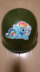 Size: 1152x2048 | Tagged: artist needed, safe, rainbow dash, pegasus, pony, cupcake, female, flying, food, helmet, irl, mare, open mouth, photo, smiling, solo