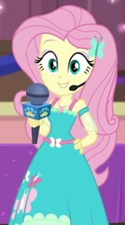 Size: 329x590 | Tagged: safe, screencap, fluttershy, best in show: the victory lap, equestria girls, equestria girls series, spoiler:eqg series (season 2), clothes, cropped, cute, dress, geode of fauna, hand on hip, looking at you, magical geodes, microphone, shyabetes, smiling, smiling at you, solo