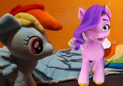 Size: 1438x1005   Tagged: safe, editor:dreamy orange, pipp petals, rainbow dash, pegasus, g4, g5, my little pony: a new generation, spoiler:my little pony: a new generation, augmented reality, female, looking at you, mare, mlp fim's eleventh anniversary, one eye closed, plushie, wink, winking at you