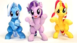 Size: 1024x576 | Tagged: safe, artist:nekokevin, starlight glimmer, sunset shimmer, trixie, pony, unicorn, series:nekokevin's glimmy, bipedal, female, frog (hoof), irl, magical trio, mare, open mouth, photo, plushie, simple background, smiling, trio, underhoof, white background